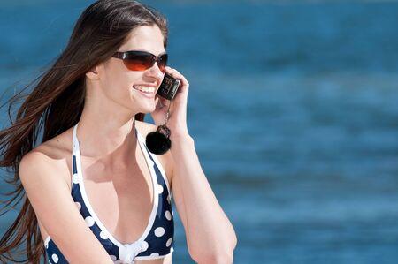 Joven mujer sonriente hablando por tel�fono en una playa Foto de archivo - 13622201