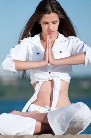 Young beautiful woman practicing yoga on the beach photo