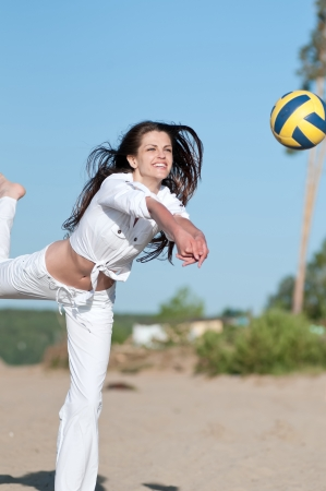 beach volley: Young beautiful woman playing volleyball on beach
