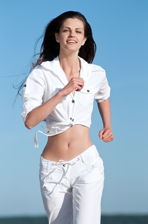 Beautiful young sport woman running in sea coast on sunny summer day Stock Photo - 13622142