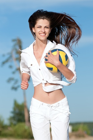Young beautiful woman playing volleyball on beach. Run with ball Stock Photo - 13621675