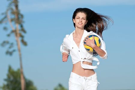Young beautiful woman playing volleyball on beach. Run with ball photo