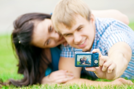 Young emotional happy teenage couple taking picture on grass in city park Stock Photo - 13622118