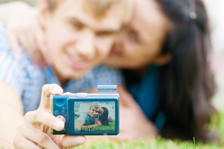 Young emotional happy teenage couple taking picture on grass in city park Stock Photo - 13622171
