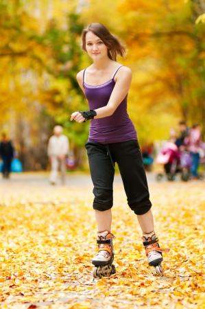 rollerblading: mujer joven feliz en patines en el parque de otoño
