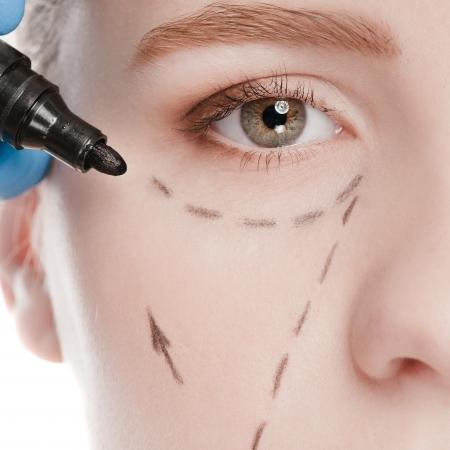 Esthéticienne toucher et tracer des lignes de correction sur le visage de la femme. Avant operetion chirurgie plastique. Isolé sur fond blanc Banque d'images
