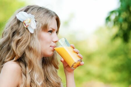 Young happy smiling woman drinking orange juice outdoor Stock Photo - 13947293