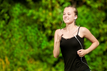 Beautiful young woman running in green park on sunny summer day photo