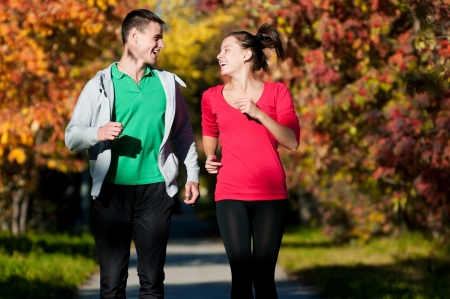 Young fitness couple of man and woman jogging in park  Standard-Bild