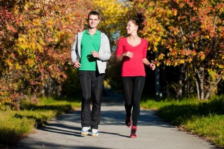 Young fitness couple of man and woman run in park  Stock Photo