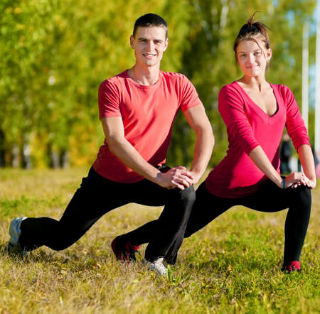 Young man and woman woman doing yoga in the sunny summer park Stock Photo - 13947243