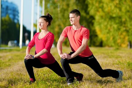 Young man and woman woman doing yoga in the sunny summer park Stock Photo - 13947286