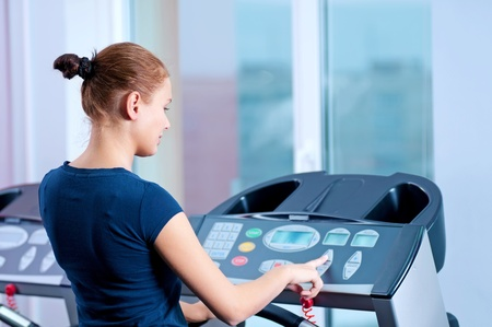 Young woman at the gym exercising. Run on machine photo