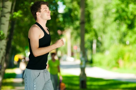 Young man jogging in park. Health and fitness. photo