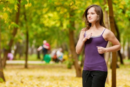 Young woman running outdoors on a lovely sunny winter (fall) day photo