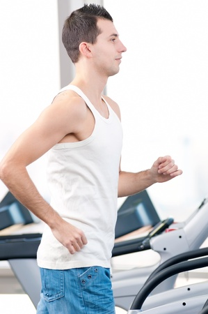 Young man at the gym exercising. Run on on a machine. Stock Photo - 14345792