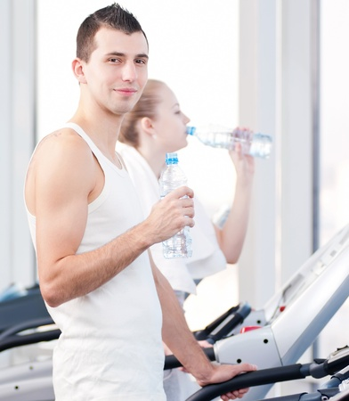 Man and woman drinking water after sports. Fitness gym. Stock Photo - 14345782