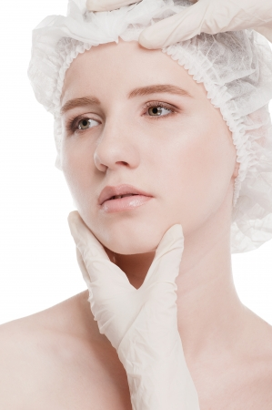 Medical examination face of beautiful woman by hands in glove - close-up portrait isolated on white  photo