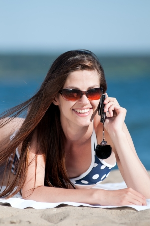Young smiling woman talking by phone on a beach photo