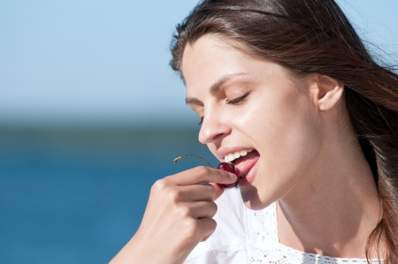 Young woman relaxing on beach and eating fruits. Red cherry Stock Photo - 15262751