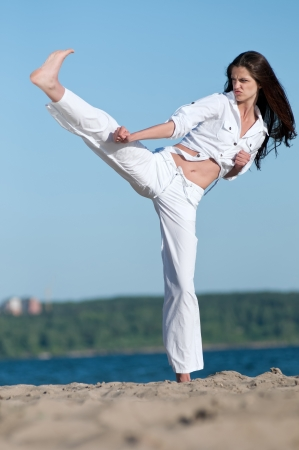 An athletic woman performing a kick in an sand beach