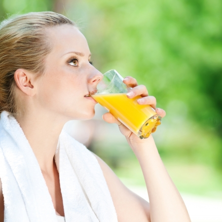 Young woman drinking orange juice after fitness exercise photo