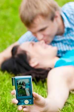 Young emotional happy teenage couple taking picture on grass in city park Stock Photo - 15262733