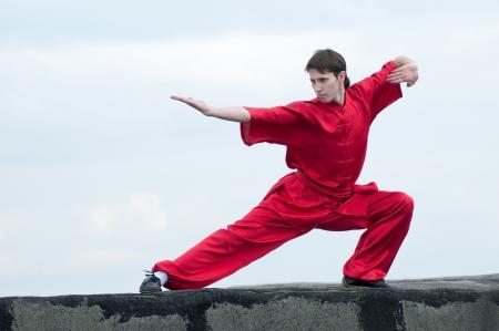 artes marciales: Shaolin guerreros wushoo hombre rojo al aire libre en la práctica del arte marcial. Kung fu