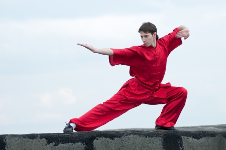 kung fu: Shaolin warriors wushoo man in red practice martial art outdoor. Kung fu