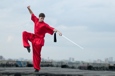 Shaolin warriors wushoo man in red with sword practice martial art outdoor. Kung fu photo