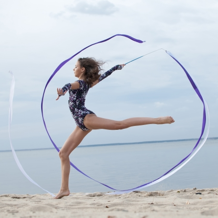female gymnast: young professional gymnast woman dance with ribbon - outdoor sand beach