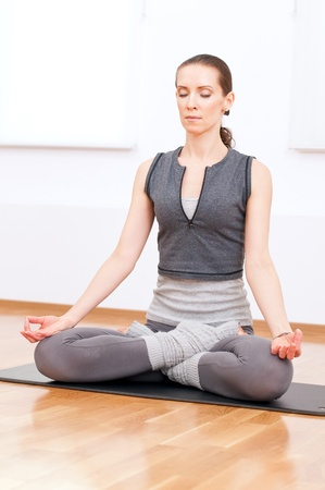 Beautiful sport woman doing stretching fitness exercise at sport gym. Yoga lotus pose Standard-Bild