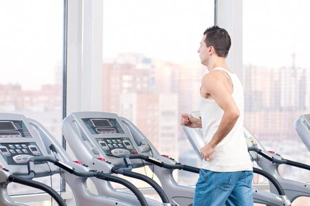weight machine: Young man at the gym exercising. Run on on a machine.