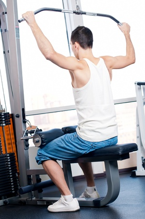 Young man doing exercises with sport equipment at gym club photo