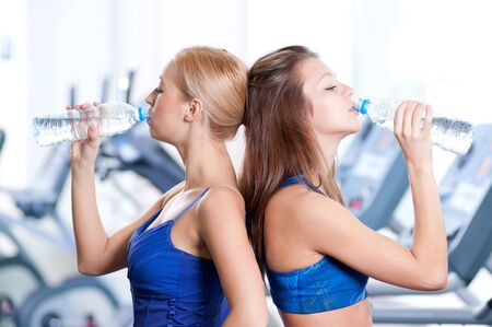 Two young women drinking water after sports. Fitness gym. Stock Photo - 15262739