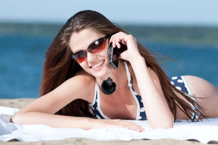 Young smiling woman talking by phone on a beach Stock Photo - 15620038
