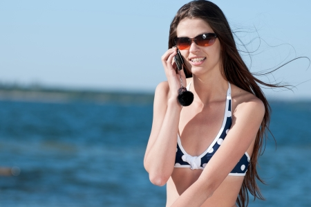 roaming: Young smiling woman talking by phone on a beach
