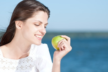 Young woman relaxing on beach and eating fruits.Green apple photo