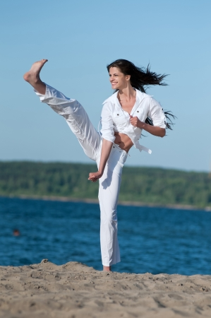 kung fu: An athletic woman performing a kick in an sand beach