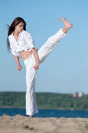 An athletic woman performing a kick in an sand beach photo