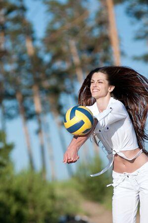 Mujer hermosa joven que juega a voleibol en la playa photo