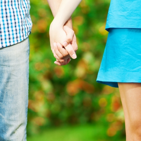 Concept shot of friendship and love of man and woman: two hands over green nature park