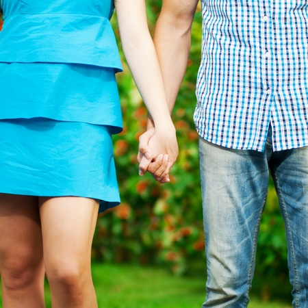 Concept shot of friendship and love of man and woman: two hands over green nature park photo