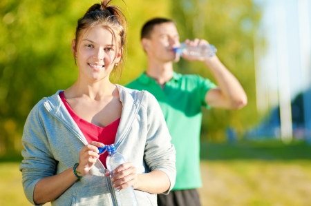 gymnastics sports: Man and woman drinking water from bottle after fitness sport exercise