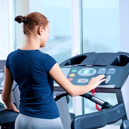 Young woman at the gym exerce. Jog on machine photo