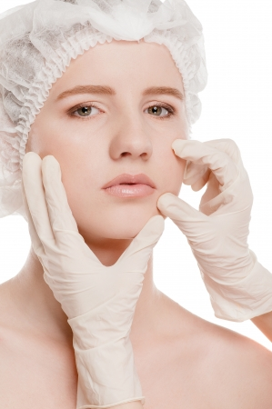 Medical examination face of beautiful woman by hands in glove - close-up portrait isolated on white  Stock Photo - 15620066