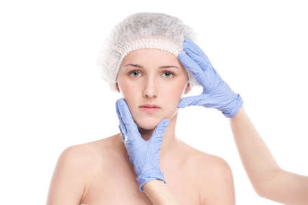 Medical face examination of beautiful woman by hands in glove - close-up portrait isolated on white photo