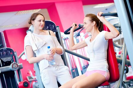 Woman doing fitness training on a butterfly machine with weights in a gym with friend Stock Photo - 15620040
