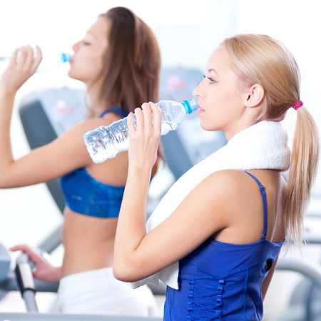 Two young women drinking water after sports. Fitness gym. Stock Photo - 15635406