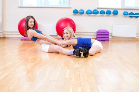 Two smiling women do stretching exercise in sports club. Fitness gym Stock Photo - 15635425